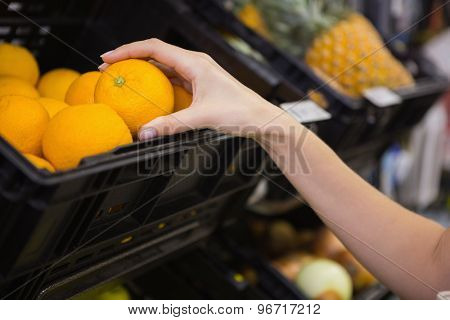 Smiling pretty blonde woman buying oranges at supermarket
