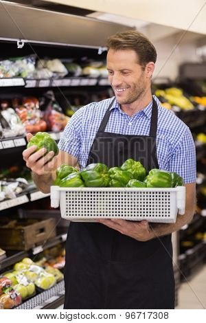 Smiling handsome worker taking a box with vegetables in supermarket