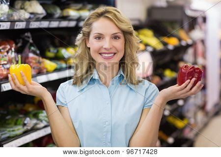 Portrait of a smiling blonde woman having a vegetable on her hands in supermarket