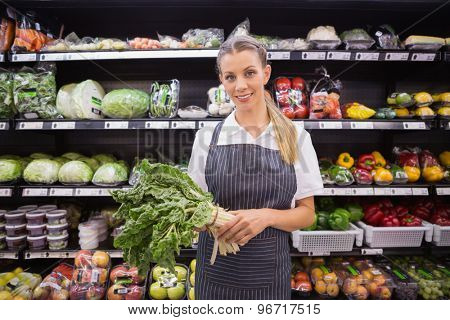 Pretty blonde woman holding vegetable and looking at camera in supermarket