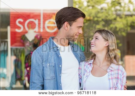happy couple standing in front of a SALE sign at the mall