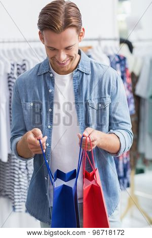 A happy smiling man with shopping bags in a clothing store