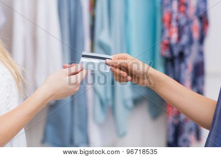 Girls handing a credit card at the clothing store