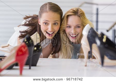 Two excited women looking at heel shoes in shoe store