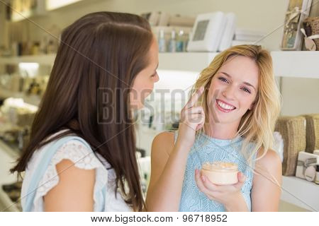 Happy blonde woman applying cosmetic products in a beauty salon