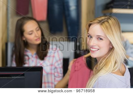 Smiling blonde doing shopping and looking at camera in clothes store