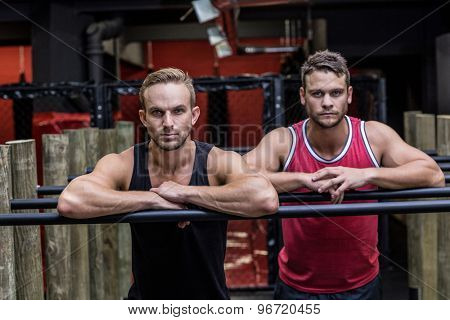 Portrait of two muscular men on a parallel bar
