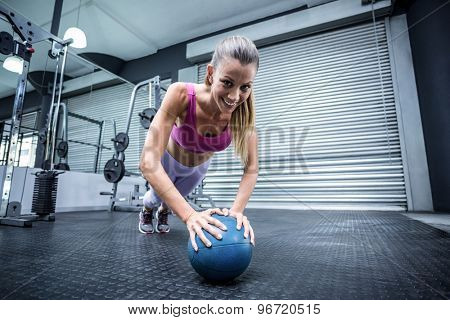 Muscular woman on a plank position with a balance ball