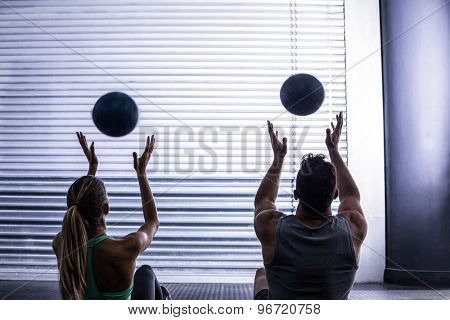 Back view of muscular couple throwing ball in the air