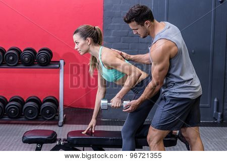 Trainer supervising a muscular woman lifting a dumbbell