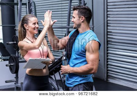 Female coach giving high five with a muscular man
