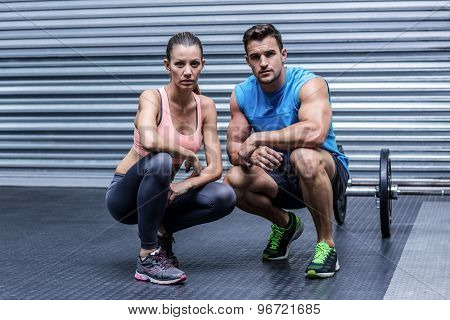Portrait of a muscular couple in a squatting position