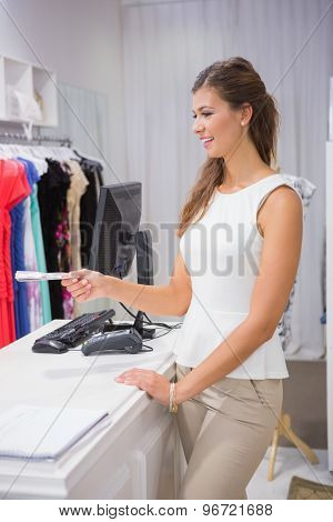 Smiling woman paying with cash at a boutique