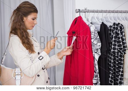 Concentrated woman taking a photo of price tag at a boutique