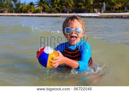 little boy playing ball on beach