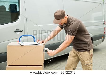 Delivery Man Scanning Boxes With Barcode Scanner