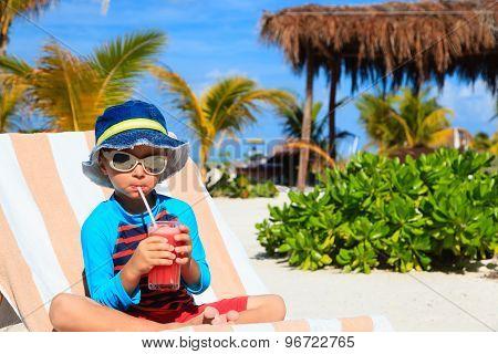 little boy drinking juice on tropical beach