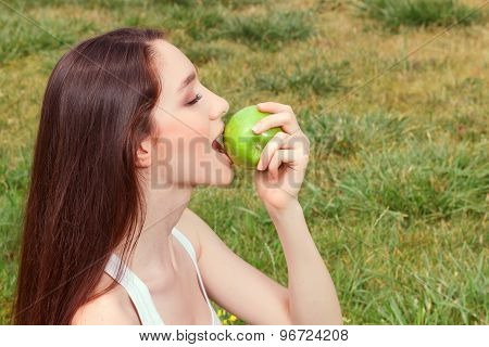Nice young girl eating apple