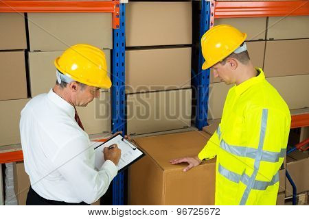 Warehouse Worker Checking The Inventory With Manager