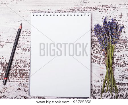 Empty Notepad, Pensil And Lavender Flowers On The Whitw Wooden Background