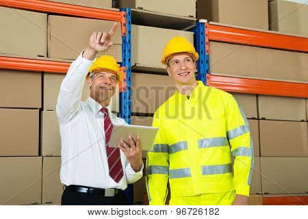 Warehouse Worker And Manager Checking The Inventory