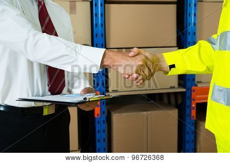Close-up Of Businessman And Warehouse Worker Shaking Hands