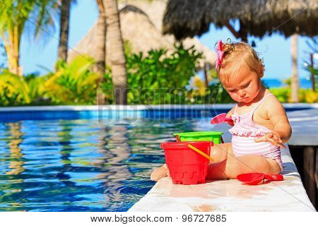 cute toddler girl playing in swimming pool at beach