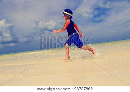 little boy running on summer beach