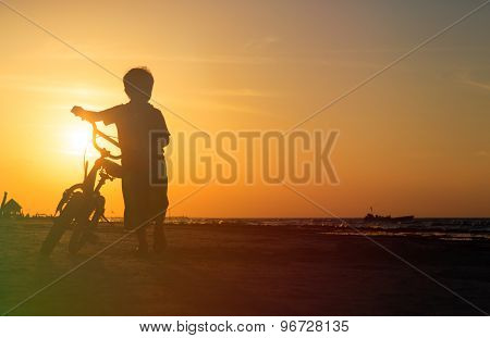 little boy riding bike at sunset