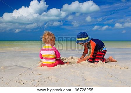 brother and sister playing with sand on beach