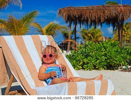 little girl drinking juice on tropical beach