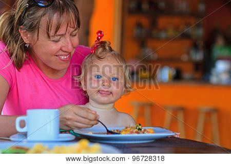 mother feeding infant daughter in cafe