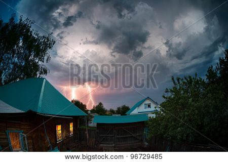 Thunderbolt over houses in the village at twilight