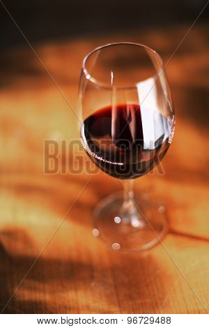 Glass of red wine on old wooden table. Very short depth of field.