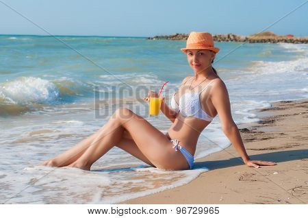 girl on the beach with a cocktail