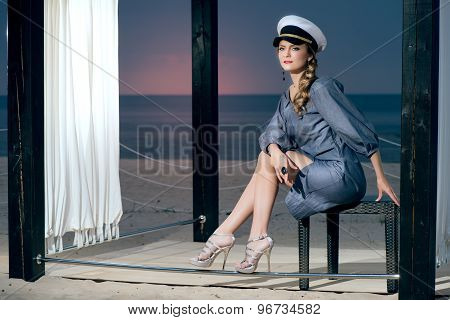 Attractive beautiful woman in captain hat on the beach