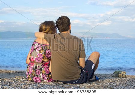 Young Couple Sitting Together On A Rocky Beach And Looking At The Seaside