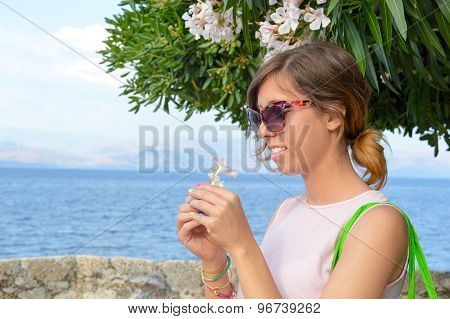 Brunette Girl Holding A White Flower With Seaside In Background