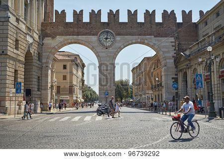VERONA, ITALY - JULY 11: Pedestrians walking by arch gateway with clock tower at the entrance of Piazza Bra, in Corso Porta Nuova. July 11, 2015 in Verona.