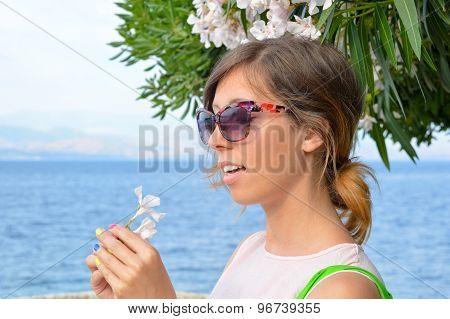 Brunette Girl Holding A White Flower With Seaside In Background
