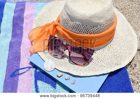 Straw Hat, Sunglasses And A Book On The Beach