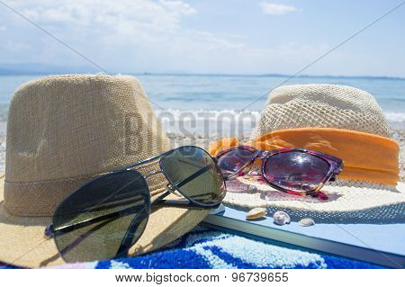 Pair Of Straw Hats, Sunglasses And A Book On The Beach With Sea In Backgound