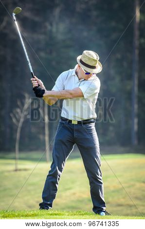 Golfer hitting golf shot with club on course