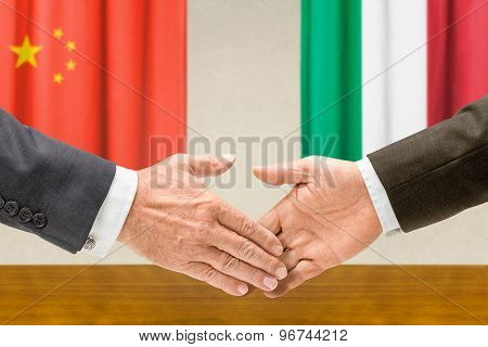 Representatives Of China And Italy Shake Hands