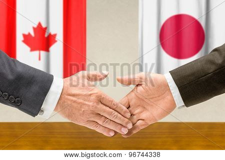 Representatives Of Canada And Japan Shake Hands
