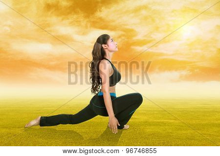 Woman Doing Yoga Exercise On Grass With Sky At Sunset