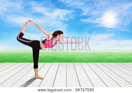 Young Woman Doing Yoga Exercise On Wood Floor