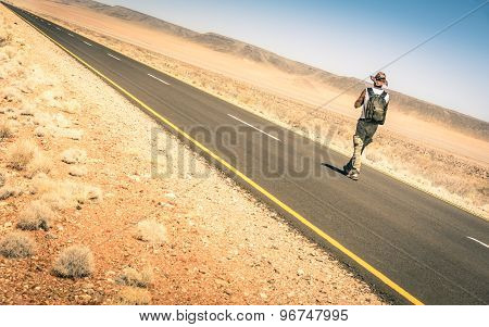 Lonely Man Walking Along The Road Among The Namibian African Desert - Alternative Lifestyle Concept