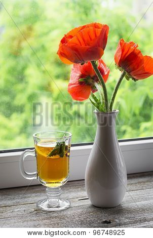 Green Tea With Lemon And Mint And Poppies In A White Vase On A Light Wooden Background