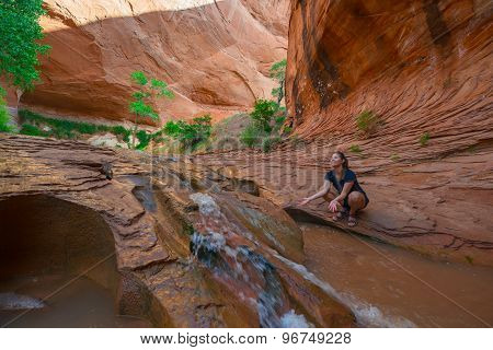 Happy Hiker Splashing Water In Beautiful Cascade In Coyote Gulch